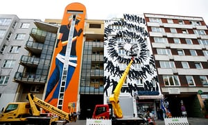 Artist David de la Mano works on a painting on a building near the museum.