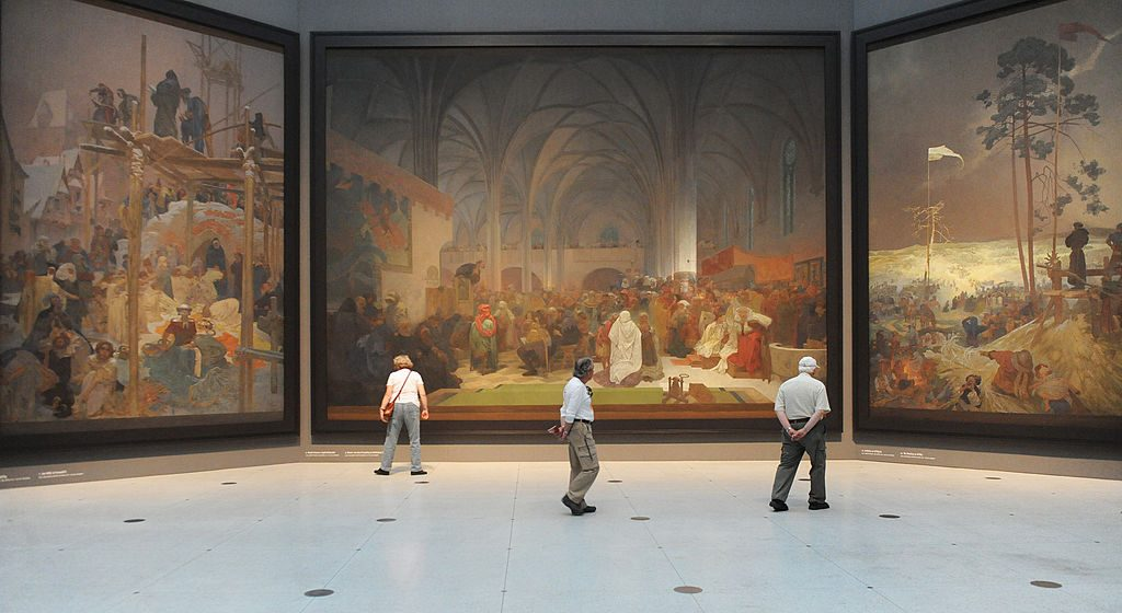 Visitors look at paintings of the